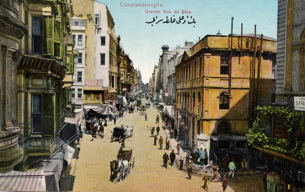 Rue de Pera, now known as Istiklal Street, at its intersection with Sahne Sokak. On the streetcorner on the left side you can see the words cafe, likely in the location of a cafe owned by François Vallaury, the father of architect Alexander Vallaury (photo: SALT Open Archive)